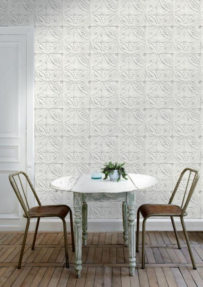 papier peint intissé en blanc aux motifs plaques Victoriennes, table en blanc avec deux chaises marron, sol en parquet rustique en couleur claire
