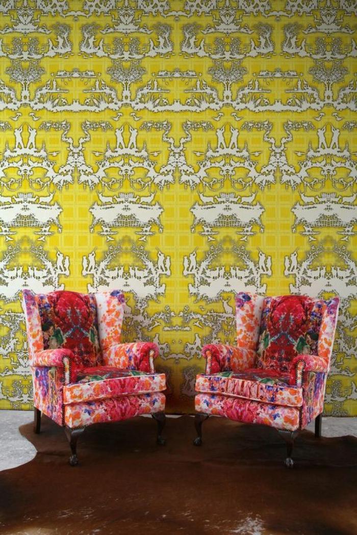 papier peint geometrique en jaune et blanc avec des motifs abstraits hallucinants, salon avec deux grands fauteuils au tissu avec des motifs floraux, avec des pieds en bois marron foncé, sol en marron et blanc