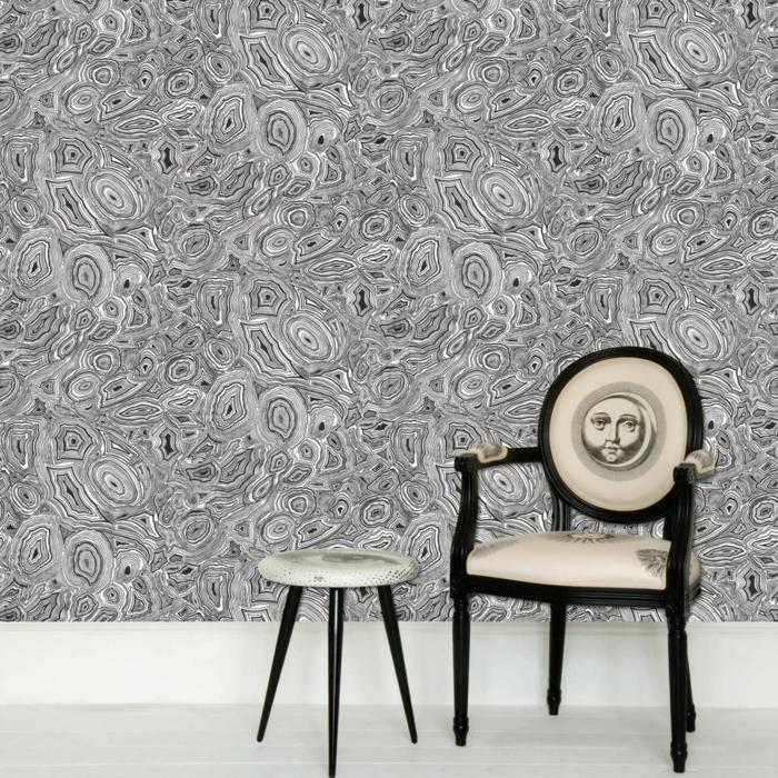 poster geant aux effets marbrés, papier peint imitation pierre, couleur grise et noire dans un salon aux meubles excentriques, fauteuil en noir et blanc, avec un visage humain sur le dossier