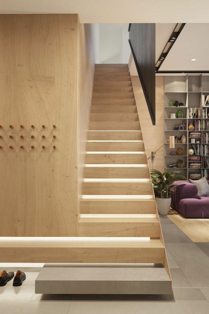 escalier design en bois clair et garde corps partiel en métal noir, première marche en béton gris, la couleur du revetement du sol du salon ouvert sur l'escalier