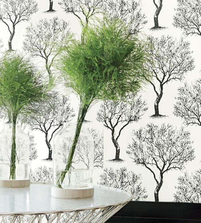 poster geant avec des arbres en noir sur fond blanc, mur d'entrée, table d'entrée en métal blanc, deux vases avec des plantes vertes en forme d'arbres, papier peint trompe l'oeil