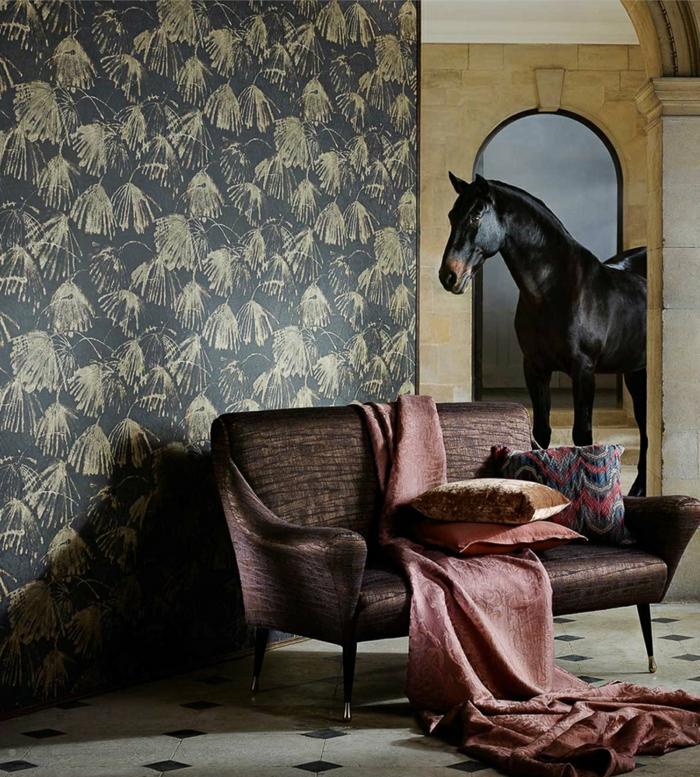 poster geant avec cheval qu sort dans une cour, mur en papier peint trompe l'oeil en bleu indigo et couleur beige, canapé couleur prune avec finition satinée avec couverture en rose poudré, sol avec carrelage en noir et blanc en style classique