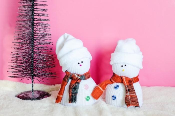 bonhomme de neige en chaussette, créer sa décoration de Noel avec matériaux simples, petites figurines diy sur tapis blanc moelleux