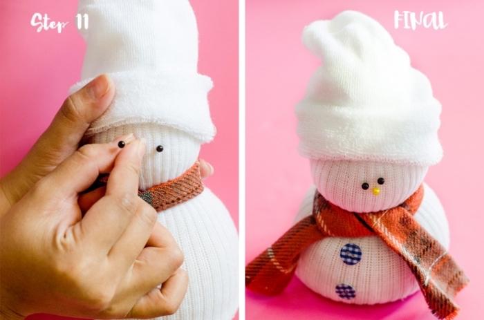 bonhomme de neige chaussette, figurine en tissu blanc avec écharpe orange et boutons bleus sur le ventre