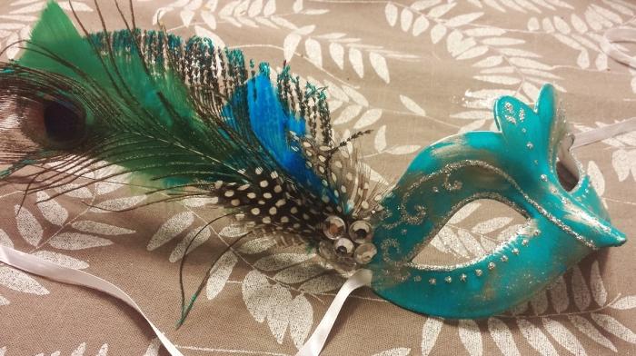 masque carnaval maternelle, modèle de masque turquoise avec décoration glitter argenté et plumes de paon