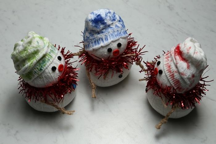 comment faire un bonhomme de neige, petits doudou fabriqués de chaussettes et décorés avec guirlande de Noel