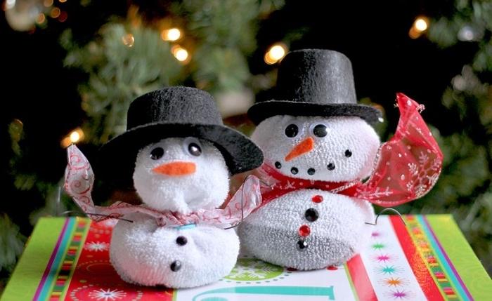 activite manuelle noel, petits bonhommes de neige en chaussures blanches avec bonnet noir et rubans rouges