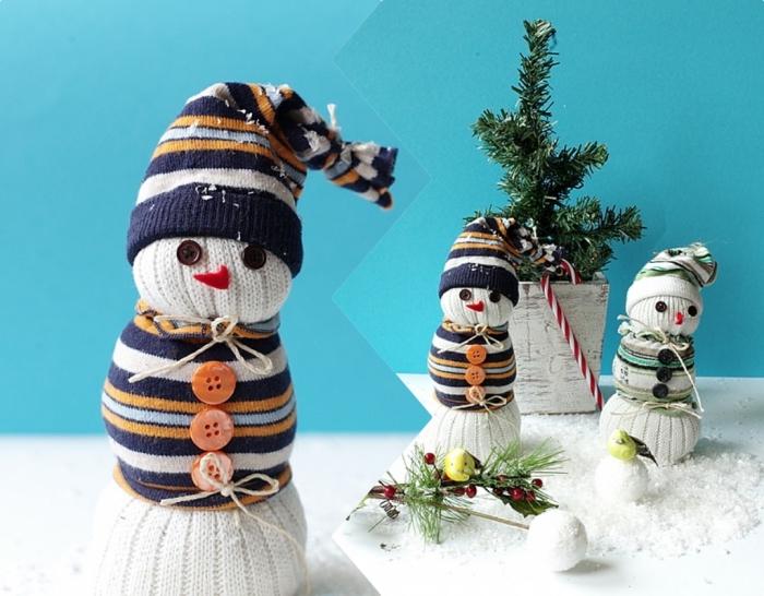 activite de noel, décoration de Noel en fond bleu avec surface blanche couverte de neige artificielle et petits bonhommes de neige diy