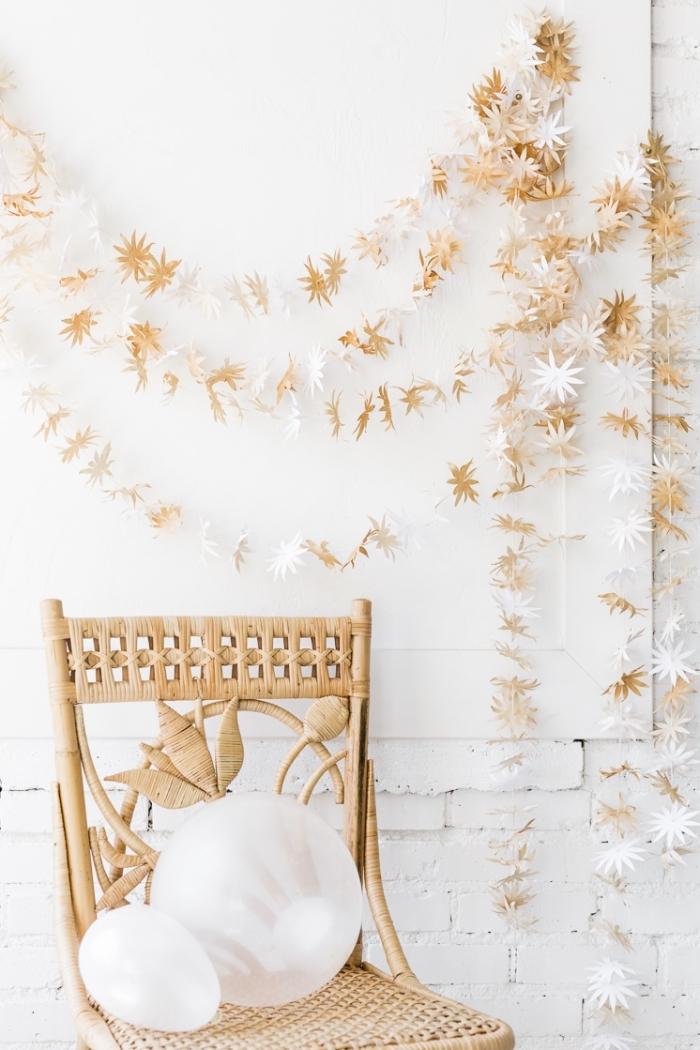 guirlande en papier crépon, aménagement de chambre blanche avec meubles en bois et déco beige