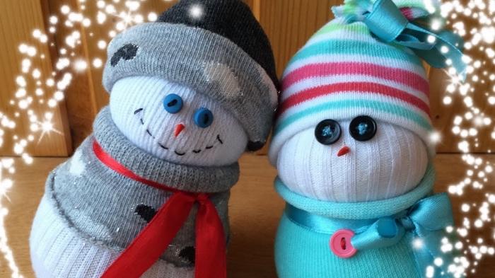 bonhomme de neige chaussette, figurine blanche habillée en gilet gris à coeurs blancs avec écharpe en ruban rouge