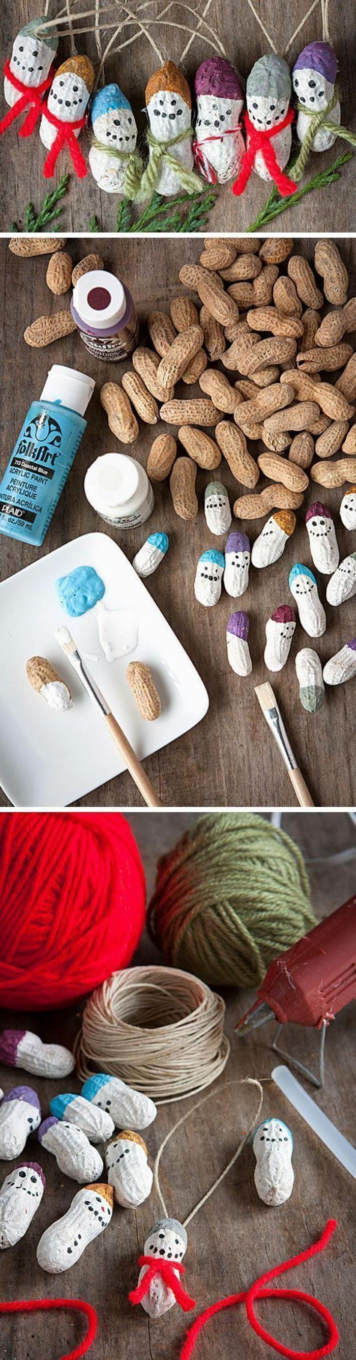 décoration de noel à faire soi même, cacahuètes peintes en blanc, avec des yeux et des bouches dessinées, suspendus sur le sapin avec des fils colorés