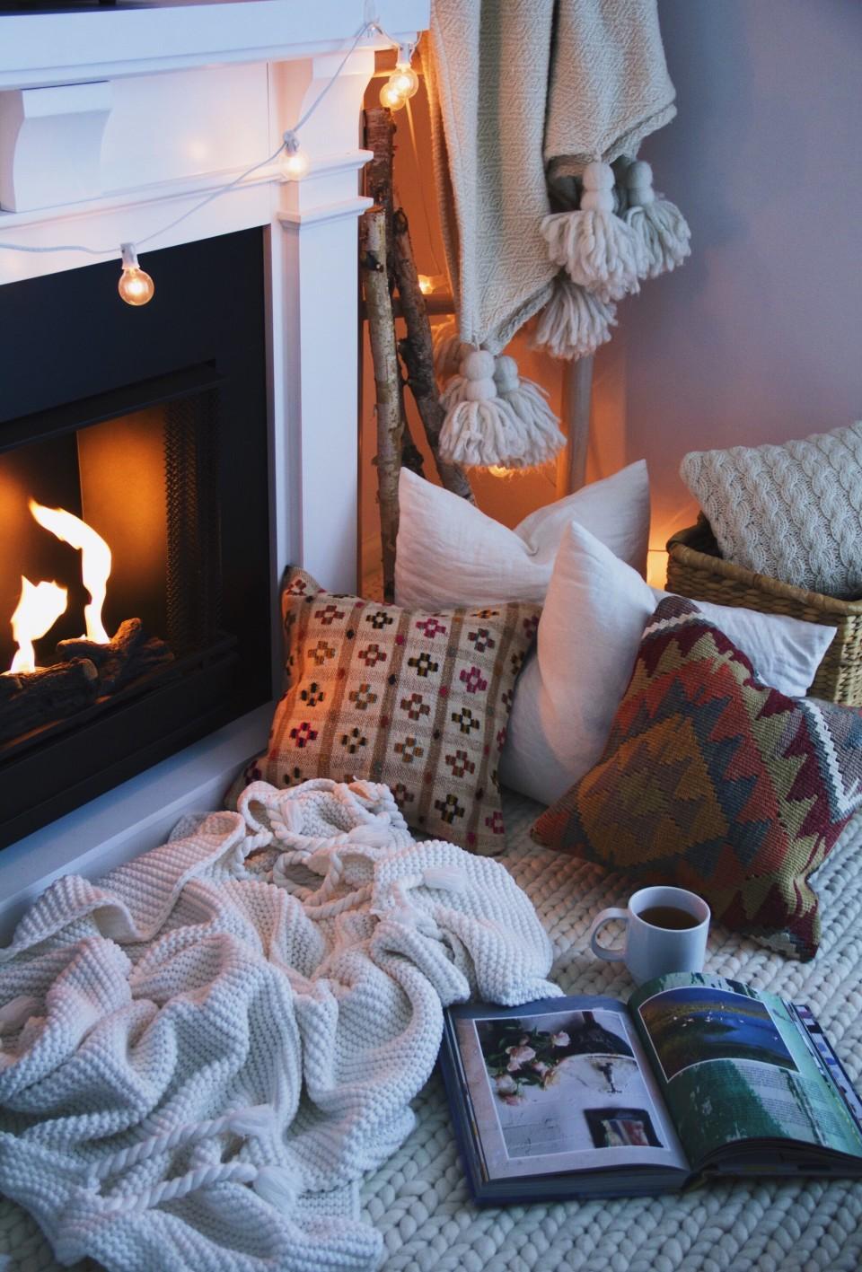 deco d'hiver, ambiance cocooning hygge, tapis grosses mailles, couverture moelleuse, guirlande lumineuse, cheminée romantique, coussins décoratifs