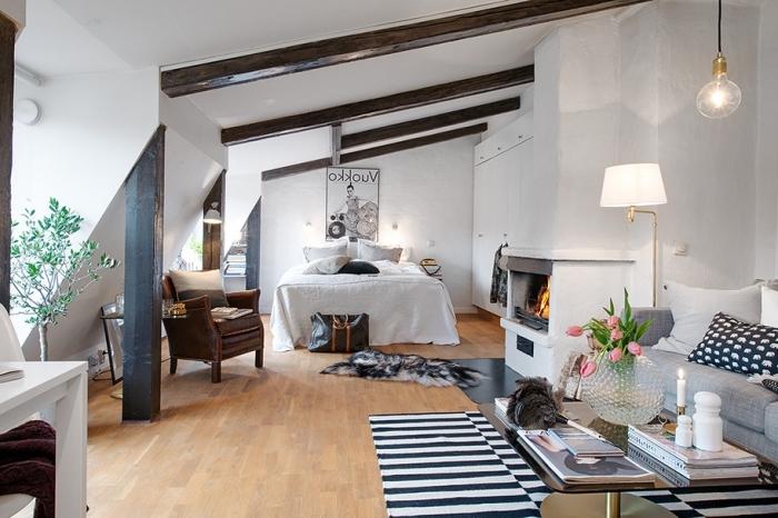 décoration chambre, chambre à coucher ouverte vers le salon, pièce dans le grenier aux murs blancs avec poutres en bois foncées
