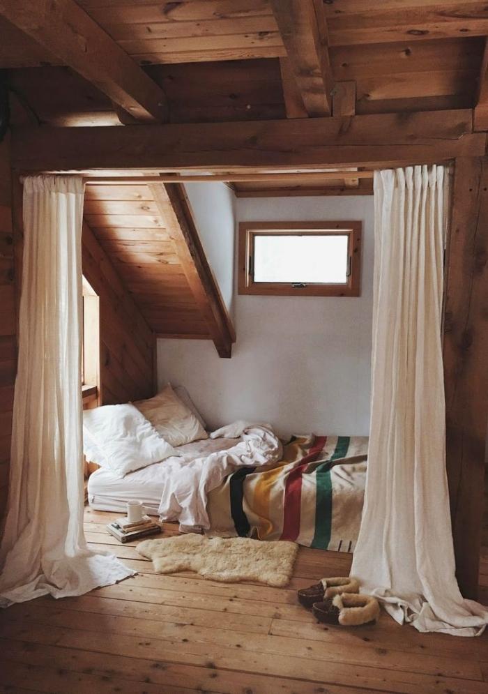 chambre mansardée, petite pièce aux murs blancs avec plafond en poutres bois foncé et petite fenêtre de bois