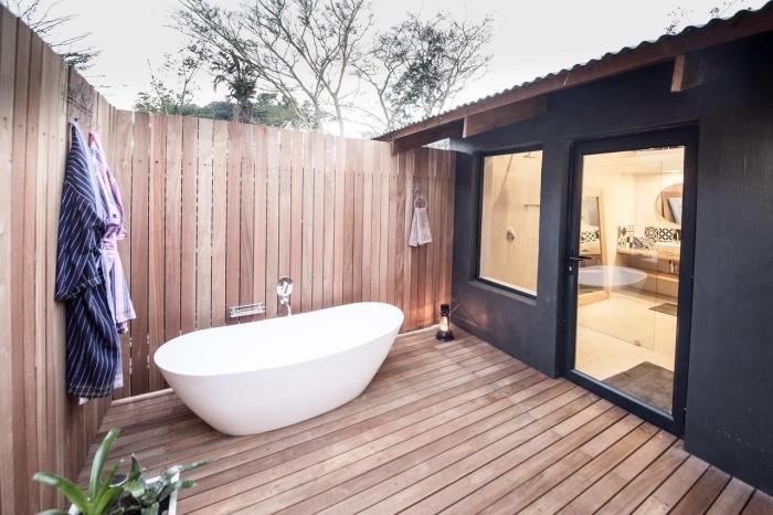 déco salle de bain extérieur avec baignoire blanche et revêtement en bois, façade maison noir avec porte et fenêtre noires