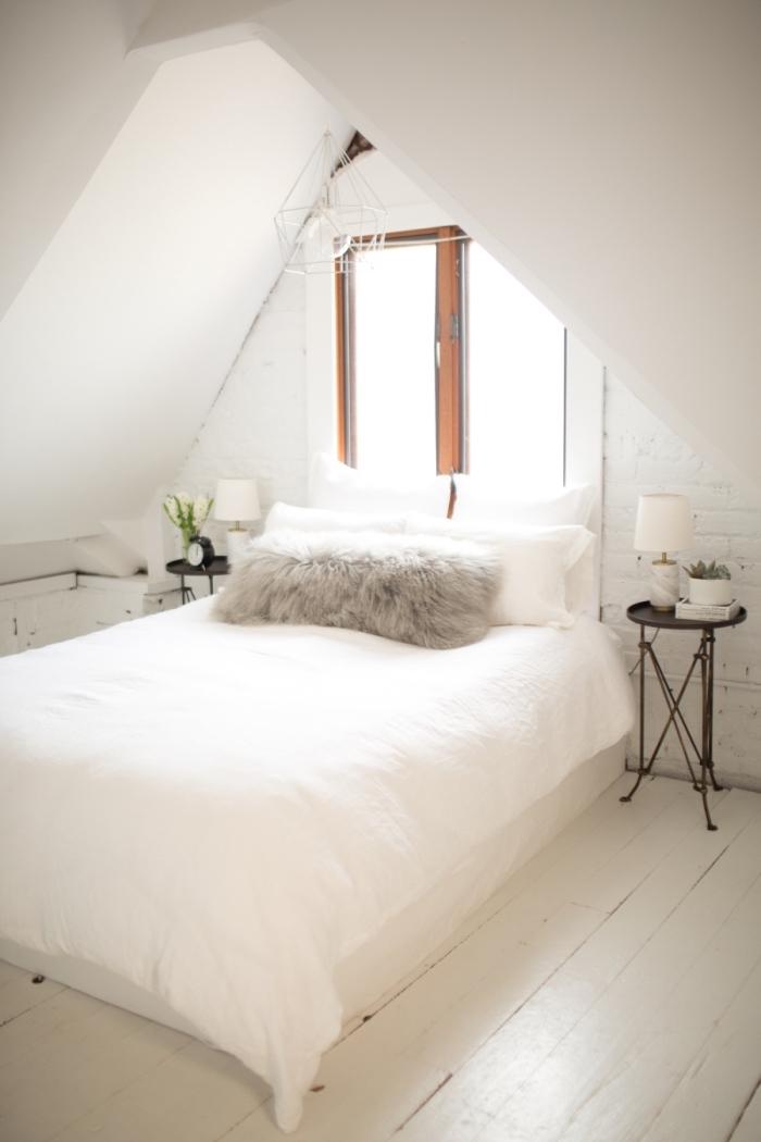 piece mansardée, chambre à coucher au grenier avec plancher blanc et petite fenêtre en bois, coussin décoratif en faux fur gris