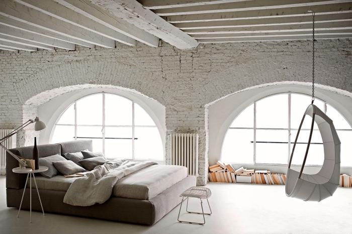 idee deco chambre mansardée, pièce aux murs en briques blanches avec plafond en poutres de bois, grand lit avec tête doux en gris