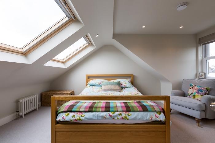 chambre a coucher, cadre et tête de lit en bois marron clair, éclairage led sur plafond blanc, couverture de lit et coussin multicolore