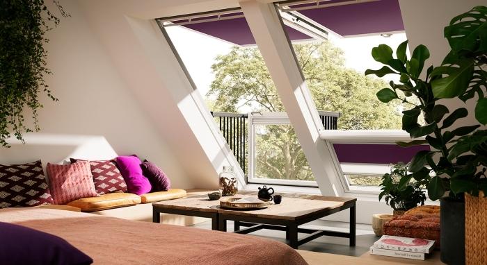chambre mansardée, modèles de coussins violet et rouge à motifs géométriques, plantes vertes suspendues