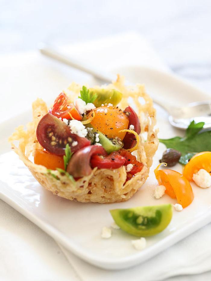 une Idée apéritif dinatoire de salade caprese arrangée joliment dans une mini tartelette au parmesan