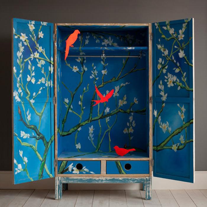 idée comment relooker armoire ancienne, repeindre un meuble en bois de couleur bleue, motif fleuri et silhouettes d oiseaux rouges