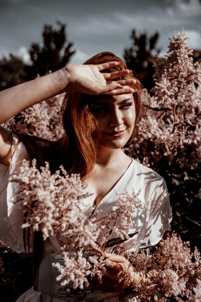 cheveux brun reflet auburn, modèle de robe blanche aux manches mi-longs et ceinture argentée, femme dans la nature