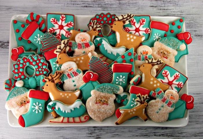 exmeple de biscuit de noel recette, idée comment faire un glacage en blanc, vert et rouge, motifs de noel, père noel, chaussette de noel, rudolphe le renne, flacons de neige et sapins