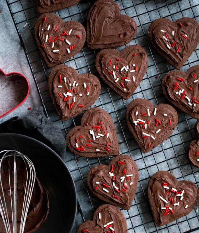 exemple glacage chocolat simple pour vos biscuits de saint valentin, sablés au chocolat en forme de coeur, couverts de vermicelles rouge et blanc