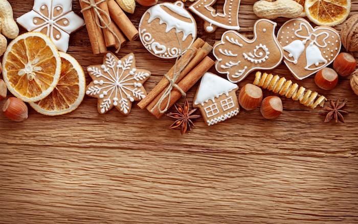 biscuits de noel en pain d épices décoré de glaçage blanc, cannelles, rondelles d orange séchées, noisettes, vanille