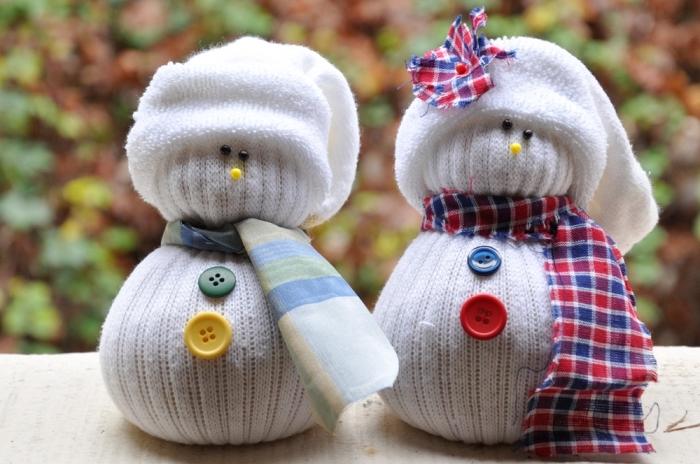 activité manuelle bonhomme de neige, figurine blanche fait à la main avec chaussette blanche et bande de tissu vert