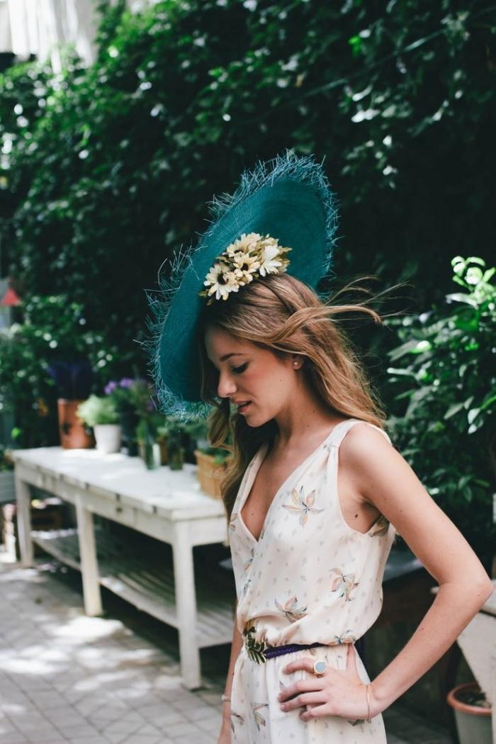 robe invité mariage, combinaison beige avec bretelle à motifs floraux et ceinture noire, capeline verte à porter avec couronne de fleurs