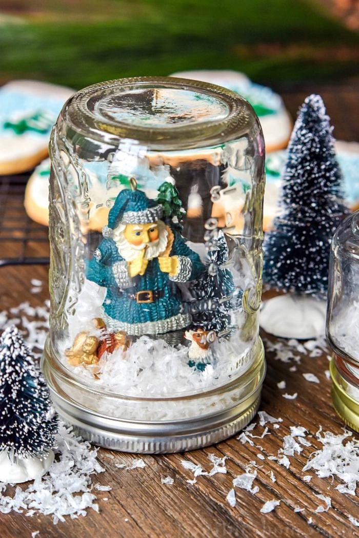 idée pour une décoration de noel à fabriquer pour adultes et enfants avec des bocaux en verre enneigés décorés de figurines de noël