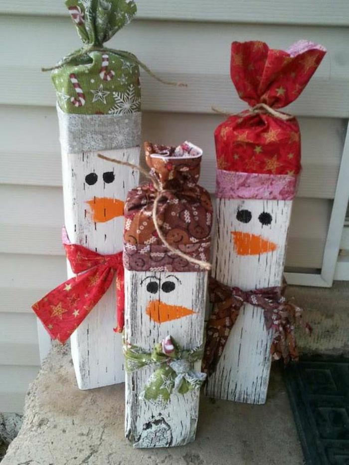 deco de noel a faire soi meme en forme de bonhommes de neige en morceaux de bois peint avec des chapeaux enroulés en papier pour empaqueter les cadeaux