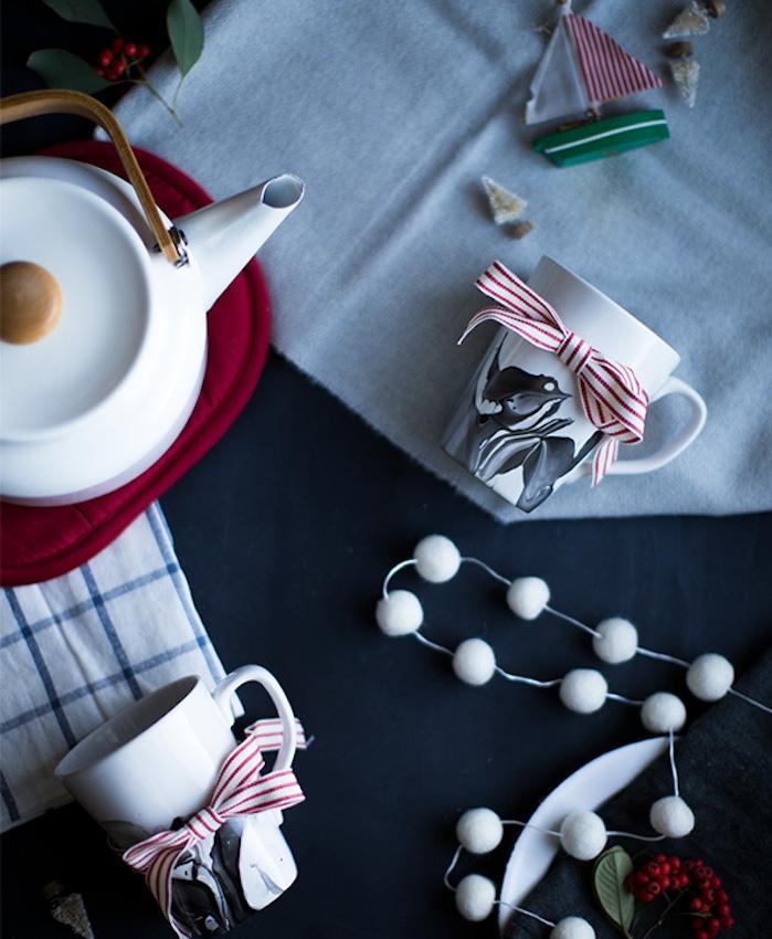 idée cadeau noel femme, tasses à café blanches à effet marbre en noir, théière blanche, décoration de noeuds de ruban rouge et blanc