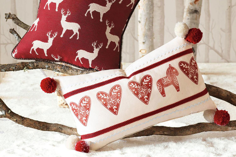 cadeau de noel pour maman, coussins rouge et blanc à motifs renne de pere noel, cheval et coeurs, pompons rouges