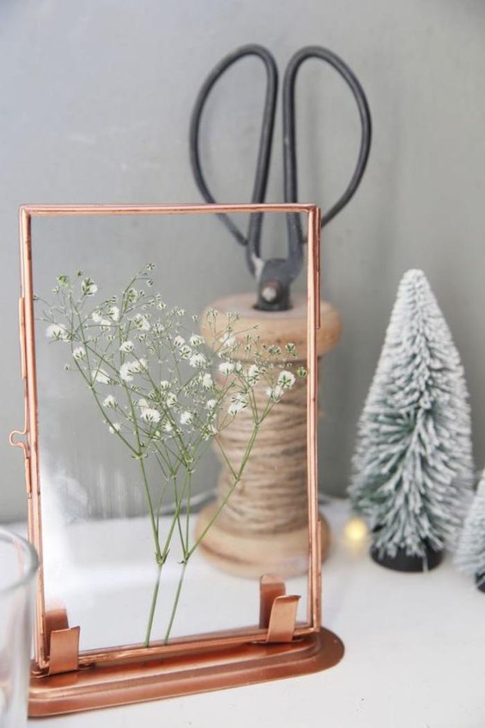 idée pour une composition florale originale sur thème noel avec une fleur sauvage sous verre et un joli cadre vintage en cuivre