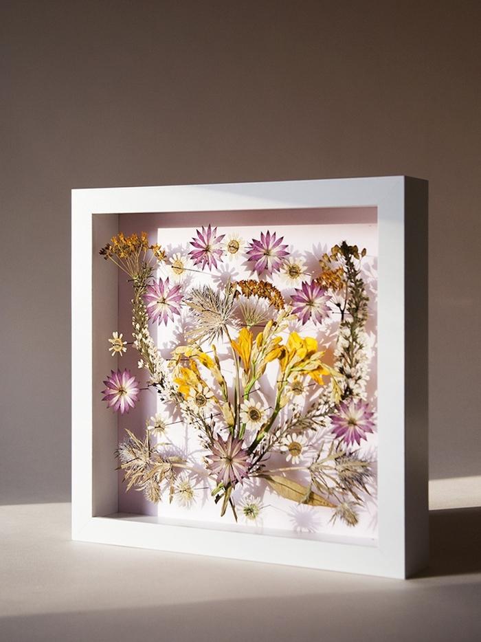 idée originale pour un activité manuelle printemps avec des fleurs pressées encadrées, joli tableau de fleurs séchées à encadrement blanc