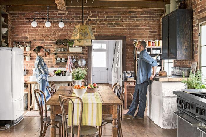 cuisine deco campagne chic avec mur en briques, table et chaises en bois brut, frigo blanc, parquet bois marron, meuble haut bleu marine patiné, etageres ouvertes