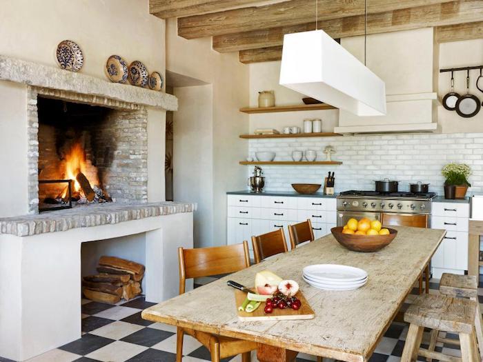 amengement cuisine rustique avec poutres apparentes, table et chaises en bois brut, cheminée en pierre, carrelage blanc et facade cuisine blanche, sol carrelage noir et blanc