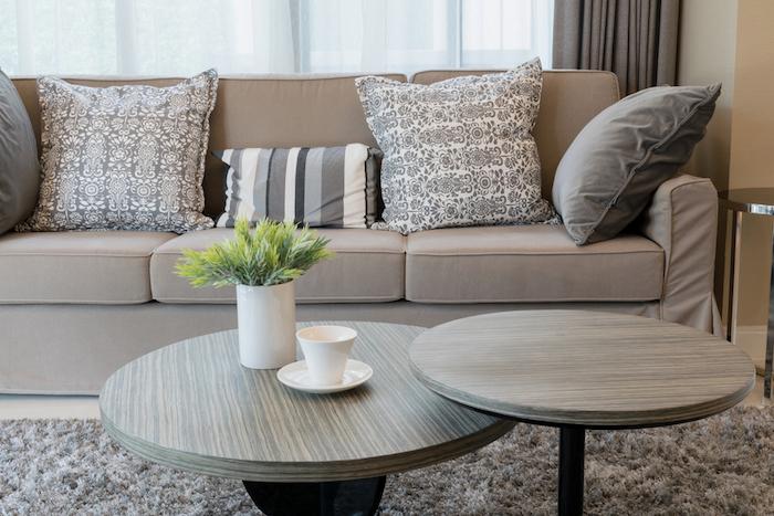 canapé couleur taupe clair avec coussins décoratifs gris et blanc, tables basses en bois, tapis gris moelleux