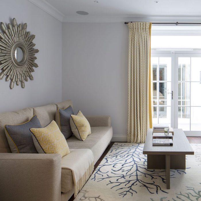 murs couleur gris perle et canapé taupe couleur décoré de coussins gris et jaunes, tapis beige à motif branches, table basse en bois, rideaux gris et blanc