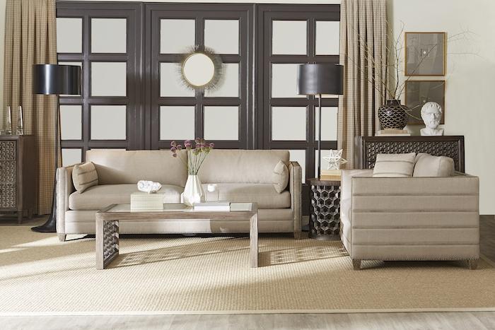 canapés et rideaux gris taupe, tapis beige, portes en bois marron et carreaux de verre, table basse en bois, lampes noires et parquet clair