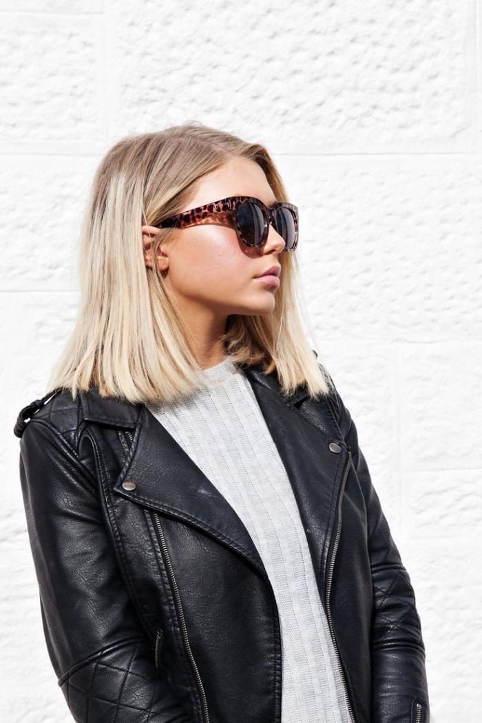 coupe cheveux mi long, tenue féminine avec blouse grise et veste en cuir noir, cheveux mi longs et raids blond blanc