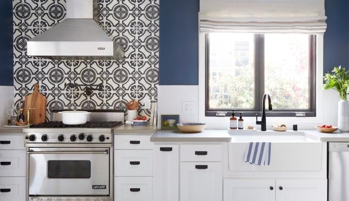 carrelage blanc, peinture murale dans la cuisine en blanc et bleu foncé, meubles de cuisine en bois peints blanc avec poignées noires