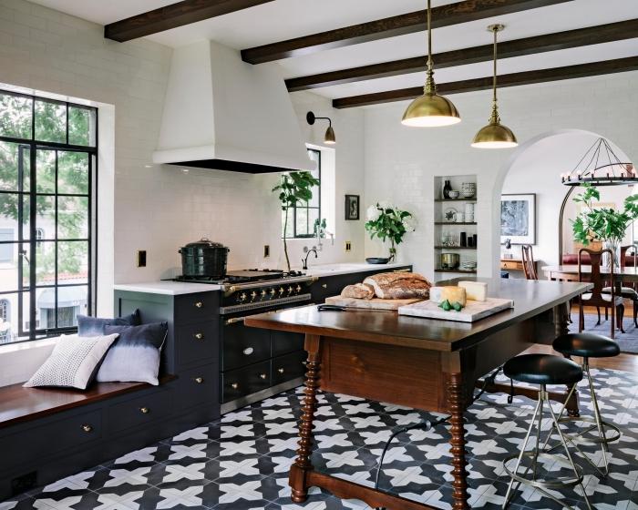 cuisine carreaux de ciment, meubles de cuisine en bois peints noir mat avec poignées dorées et comptoir blanc