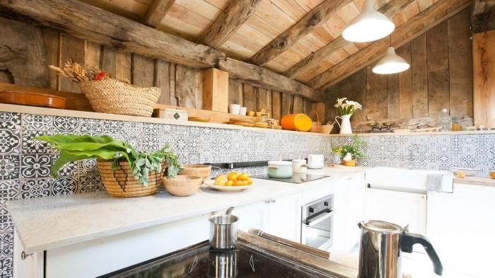carrelage mural, meubles de cuisine blancs avec comptoir marbre, plafond de bois massif avec lampes suspendues blanches