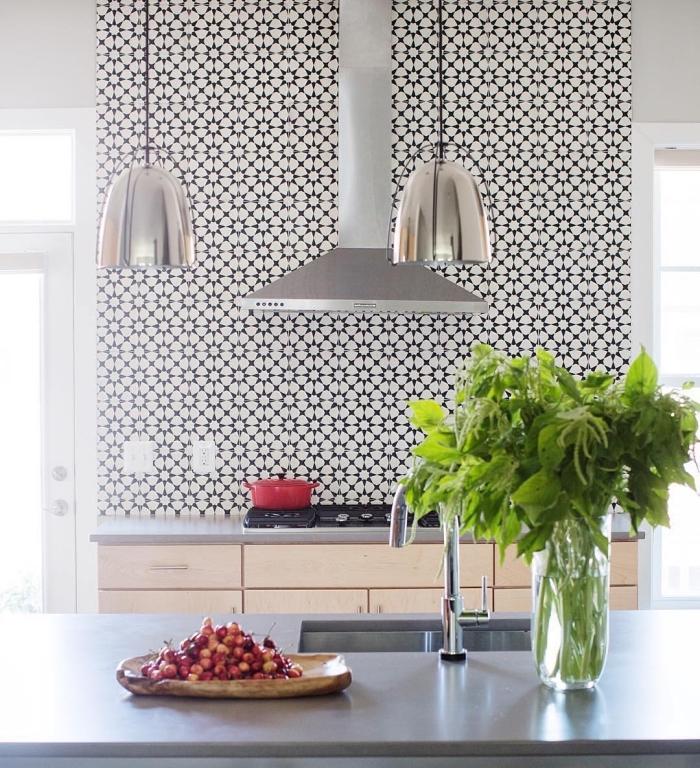 stickers carreaux de ciment blanc et noir, meubles de cuisine en bois avec comptoir gris et lampes argentées