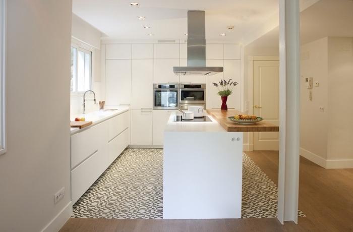carrelage ciment, aménagement de cuisine d'angle avec meubles blancs sans poignées et éclairage led