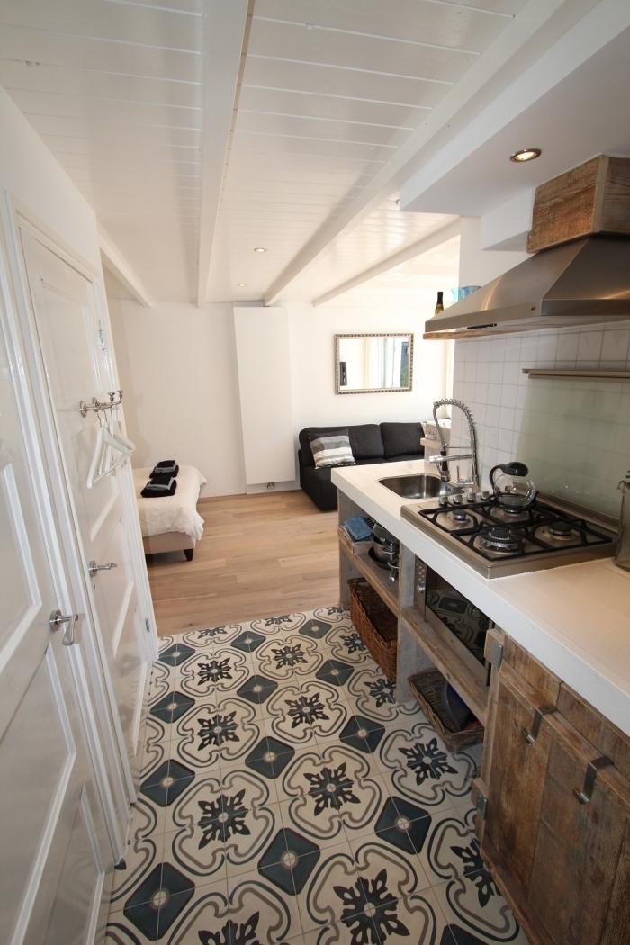 carrelage ciment sur le sol, aménagement petite cuisine en longueur ouverte sur le salon blanc