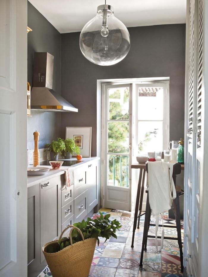 carreaux de ciment sur le sol à design géométrique et multicolore, cuisine aux murs gris foncé et meubles gris clair
